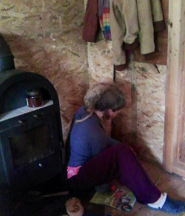 finishing putting the plywood up on the wall behind the wood stove